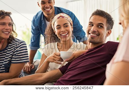 Young friends meeting and enjoying coffee after a long time. Group of happy multiethnic men and women in conversation while drinking tea. Guys and smiling girls talking and discussing at home.