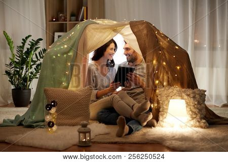 leisure, hygge, technology and people concept - happy couple with tablet pc computer in kids tent at home