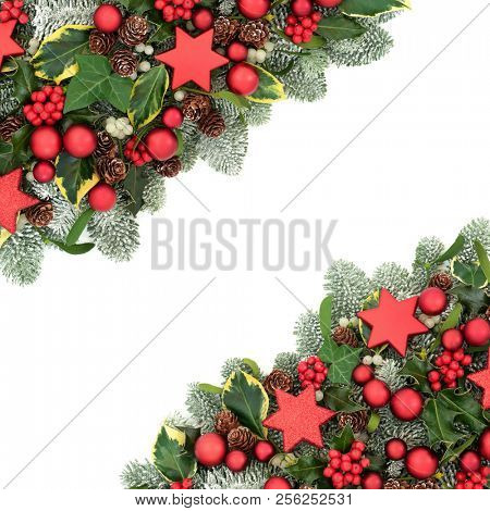 Christmas background border with red bauble decorations, winter flora of holly berries, snow covered spruce pine, ivy, pine cones and mistletoe on white background with copy space.