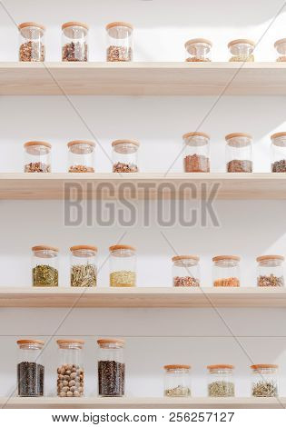 Close-up View Of Various Ingredients In Glass Containers On Wooden Shelves