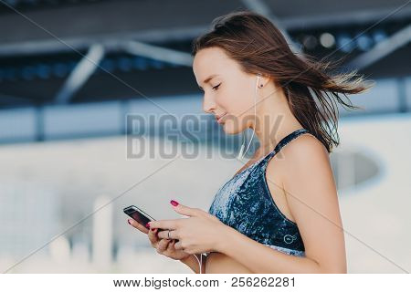 Sideways Shot Of Sporty Lovely Female With Dark Hair, Dressed In Casual Outfit, Holds Modern Smart P