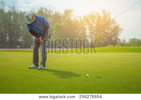 Golfer Putting Golf Ball On The Green Golf, Lens Flare On Sun Set Evening Time. Golfer Putting Golf