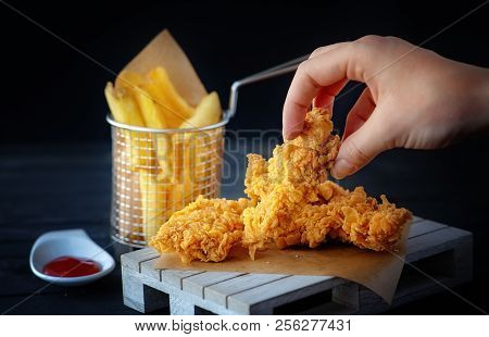 Hand Grabs Crispy Kentucky Fried Chicken French Fries And Tomato On Black Wooden Table