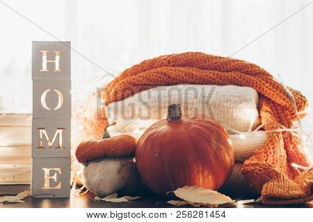 2c872cdce2 Background with warm sweaters and the inscription HOME. Pile of knitted  clothes with autumn leaves