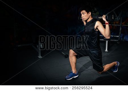 Training With Barbell, Fit Young Man In Sportswear Straining To Lift Heavy Weights During A Workout