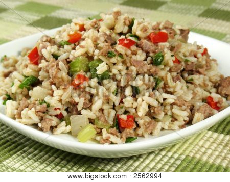 """A delicious traditional Cajun rice dish which is made """"dirty"""" from the brown color of chicken liver and gizzards. It is prepared with sausage (or ground pork/beef) bell peppers celery and onion and garnished with parsley. This is excellent as a  poster"""