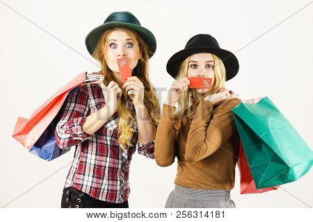 Female Friends On Shopping Showing Tag With Sale Percentage Sign Enjoying Cheap Clothing.