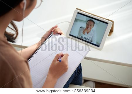 Female Student Watching Online Lesson And Taking Notes In Textbook
