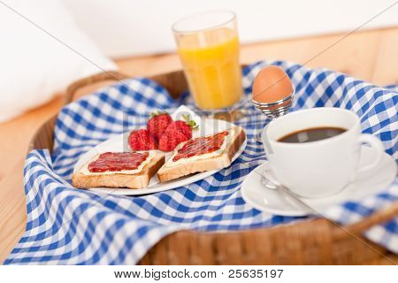 Homemade breakfast on wicker tray with checked teacloth in bedroom