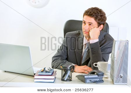 Bored Modern Businessman Sitting At Office Desk