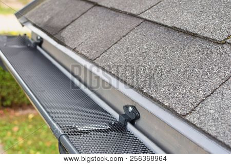 Plastic Guard Over New Dark Grey Plastic Rain Gutter On Asphalt Shingles Roof At Shallow Depth Of Fi