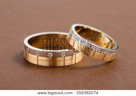 Two-tone Wedding Rings With Diamonds On Brown Background. Rose Gold And Silver Rings For Bride And G