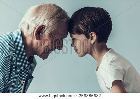 Handsome Grandpa And Grandson On Blue Background. Happy Grandfather And Grandson Looking At Each Oth