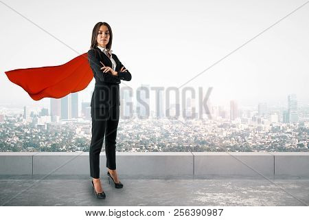 Attractive Young European Woman With Red Hero Cape And Folded Arms Standing On City Background. Supe