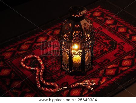Arabic lantern on red carpet with wooden rosary
