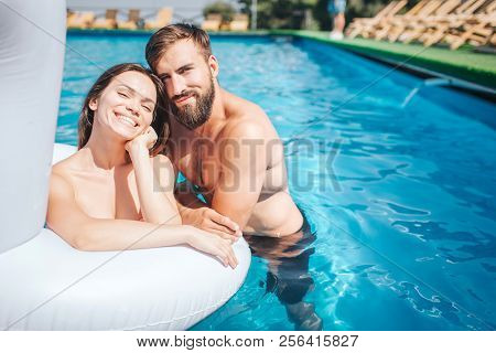 Nce And Positive Young People Are Swimming In Pool. Girl Does It In Air Matress. Guy Is Swimming In