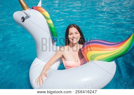 Happy Girl Is Swimming In Pool. She Is In Air Mattress That Looks Like Colorful Unicorn. She Leans T