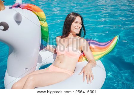 Well-built Girl Sits On Air Mattress And Looks Ti The Right. She Wears Peach Color Swim Suit. Girl I