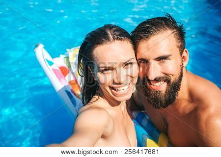 Nice And Positive Couple Taking Selfie And Look On Camera. They Smile. Girl Holds Camera. They Stand