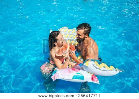 A Picture Of Couple Swimming In Pool And Leaning To Air Mattress. They Look At Each Other. Also Coup