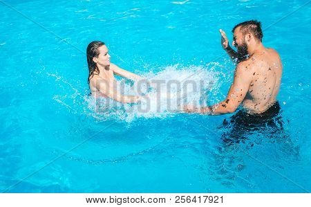Guy And Girl Are Playing In Swimming Pool. Girl Stands There And Making Water Splashing. Guy Protect