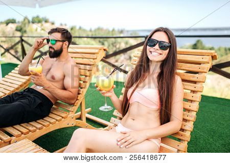 Beautiful And Well-built Couple Is Lying On Sunbeds And Having Rest. They Have Glasses Of Cocktails