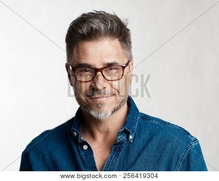 Happy smart older man in casual jeans shirt and glasses smiling isolated on white background.