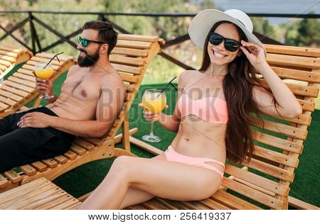 Nice Picture Of Girl And Guy Sitting On Sunbeds. She Looks On Camera And Smiles. Girl Touches Her Su