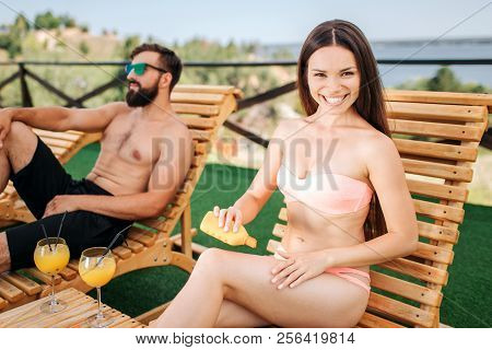 Positive Girl Sits On Sunbed With Her Boyfriend. She Looks On Camera And Smiles. Girl Puts Some Crea