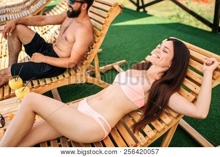 Happy Girl Is Lying On Sunbed And Smiling. She Stretches Her Body. Guy Sits Besides Her. He Looks St