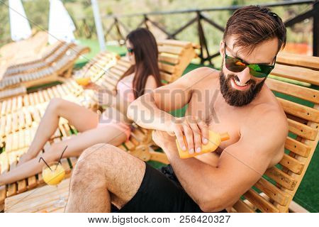 A Picture Of Bearded Guy Sitting On Sunbed And Put Some Sunproof Cream On Skin From Orange Bottle. H