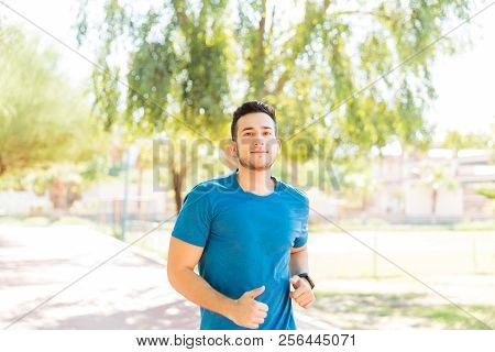 Ambitious Male Runner Working Out On Track In Park During Summer