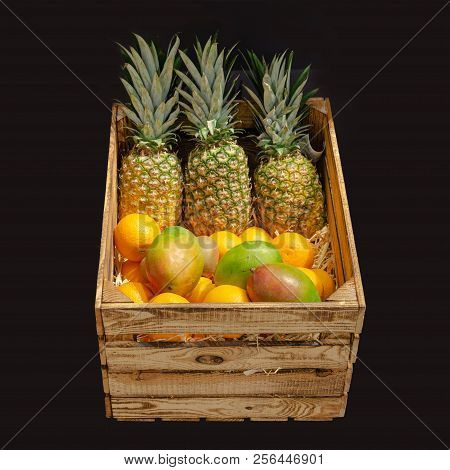 Wooden Box With Tropical Fruits Separated On Black