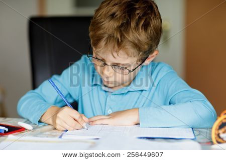 Cute Little Kid Boy With Glasses At Home Making Homework, Writing Letters And Doing Maths With Color