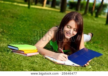 woman laying on grass and writing