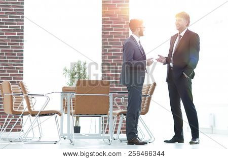 Two business executives talking about business in the office.