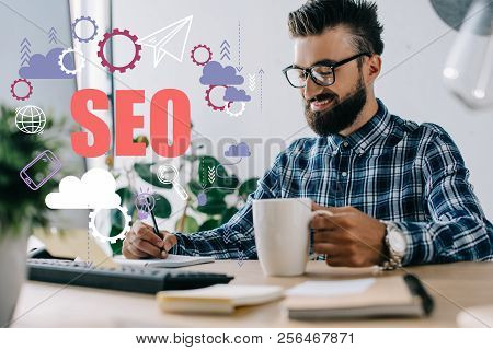 Successful Seo Manager With Cup Of Coffee And Computer Writing Notes At Workplace With Seo Icons