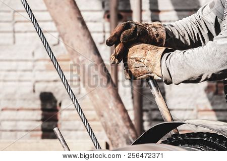 Worker Hands Pulling The Lever Of A Pile Driver (bate-estaca). Construction Worker. Two Hands Holdin