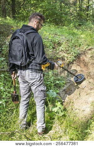 Search For Treasure, Military Items Using A Metal Detector. A Man In The Forest Searches The Area In