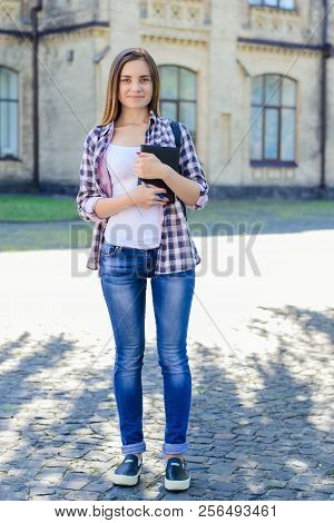 Full-length Portrait Of Happy Smiling Confident Teenage Girl In Checkered Shirt And Jeans Standing A