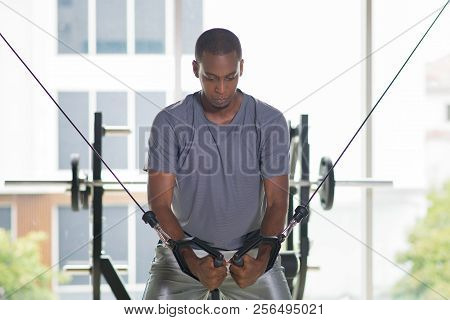 Black man exercising pecs on gym equipment. Young guy wearing t-shirt and standing with window in background. Bodybuilding concept. Front view. poster