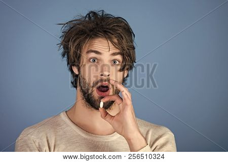 Man with surprised face hold pill. Cold, flu and headache treatment, hypnotic tablet. Health and medicine, hangover. Drug and antidepressant, insomnia. Dieting pill and vitamin, man with anabolic. poster