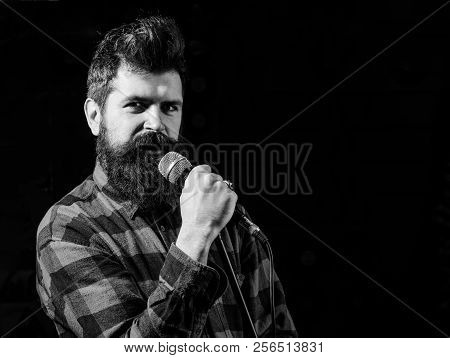 Musician, singer makes effort to win musical contest. Talent show concept. Man with tense face holds microphone, singing song, black background. Musician with beard lighted by spotlight, copy space. poster