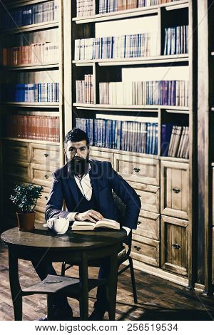 Elite lifestyle concept. Aristocrat on smiling face holds book. Man in classic suit sits in vintage interior, library, book shelves on background. Oldfashioned man near cup, teapot. poster