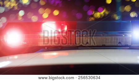 Police Patrol Car Of The Specialized Unity In The Night Time. Red And Blue Flashes On The Car Of The