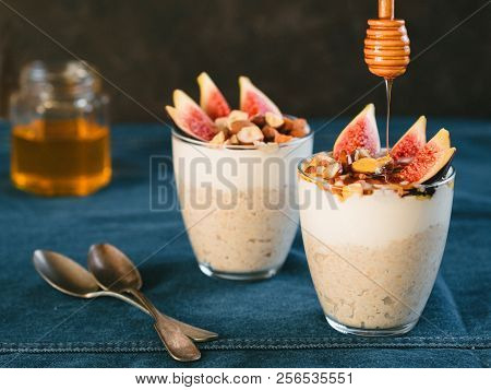 Overnight Oats With Yogurt, Figs And Nuts In Glass On Jeans Tablecloth And Black Background. Idea Re