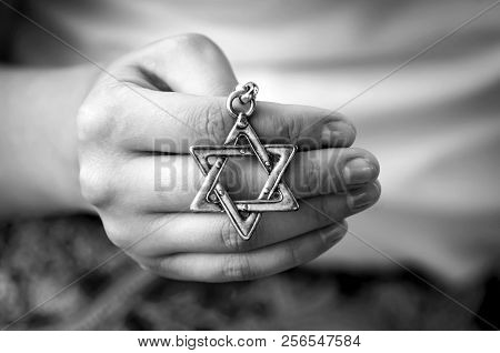 A Hand Of A Young Woman Hand Holding A Star Of David Key Chain. Black And White Image. The State Of