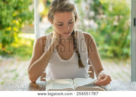 Christian Worship And Praise. A Young Woman Is Reading The Bible And Praying In The Early Morning