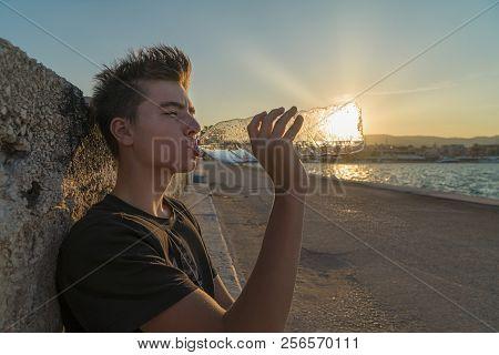Young Man Drinking Water With The Sun Behind The Bottle,