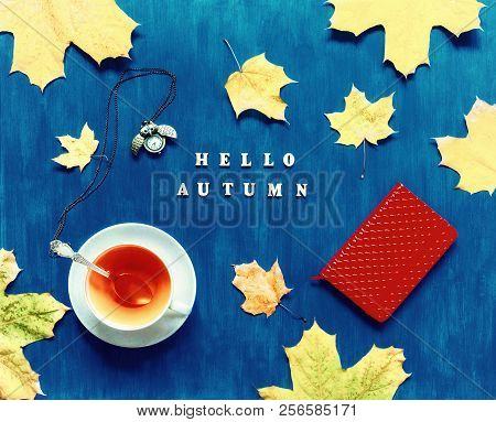 Autumn still life. Cup of tea with maple autumn leaves, metal clock, red notebook and inscription Hello autumn on the dark blue background. Autumn seasonal composition with Hello autumn concept